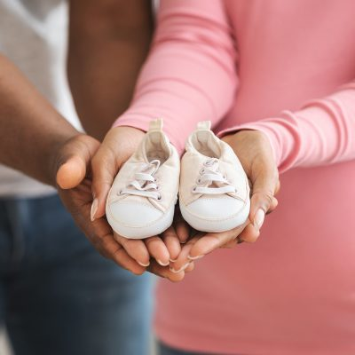 Parenthood concept. Closeup of cute baby shoes in pregnant black couple hands. Unrecognizable african american man and woman showing small shoes for their coming baby, cropped