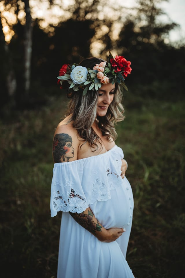 white dress maternity photo in the woods at sunset